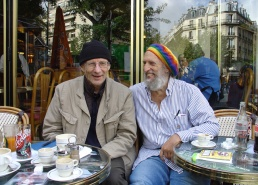 [Philippe Coupey and Lee Lozowick laughing and enjoying a cup coffee at an outdoor table of the Café de la Liberté, Paris.]