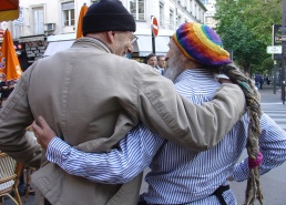 [Philippe Coupey, in khaki jacket and black ski hat, arm and arm with Lee Lozowick,  who sports a rainbow beret and a grey braid down to his waist, on the rue de la Gaité in Paris.]